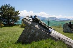 Jogador do Paintball colocado na estrutura de madeira da camuflagem Fotos de Stock