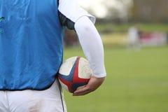 Jogador do rugby que prende uma esfera Imagens de Stock