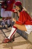 Jogador do softball que senta-se no banco com bastão fotografia de stock