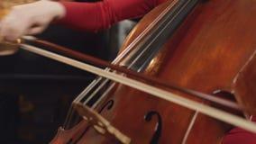 Jogador do violoncelo M?os do violoncelista que jogam o violoncelo com curva Close up do instrumento musical da orquestra do viol filme