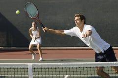 Jogador dos dobros que bate a bola de tênis com golpe foto de stock