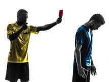 Jogador e árbitro de futebol de dois homens que mostram a silhueta do cartão vermelho Imagens de Stock Royalty Free