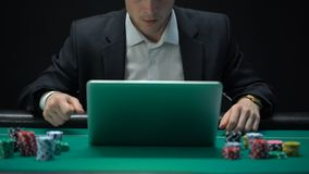 Jogador em linha do casino que aposta na aplicação do portátil, jogo perdedor, apego video estoque