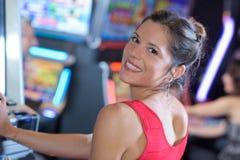 Jogador fêmea do retrato que senta-se no slot machine Fotos de Stock Royalty Free