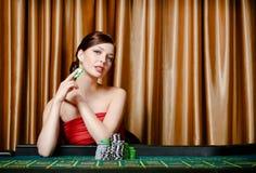 Jogador fêmea que senta-se na tabela da roleta Fotos de Stock