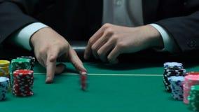 Jogador masculino afortunado que faz a primeira aposta que lanç ocasionalmente a microplaqueta, fortuna em suas mãos video estoque