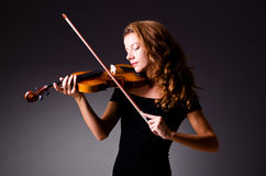 Jogador musical fêmea contra o fundo escuro Imagens de Stock