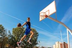 Jogador novo da rua do basquetebol que faz o afundanço Fotos de Stock Royalty Free
