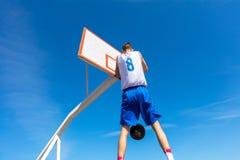 Jogador novo da rua do basquetebol que faz o afundanço Imagens de Stock