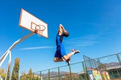 Jogador novo da rua do basquetebol que faz o afundanço Fotografia de Stock