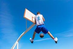 Jogador novo da rua do basquetebol que faz o afundanço Imagens de Stock Royalty Free