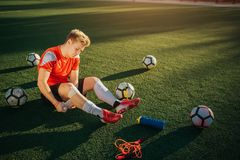 Jogador novo que senta-se no gramado e no vento em torno do pé com atadura Fá-lo cuidadoso O indivíduo é bordadura com bolas Thee foto de stock