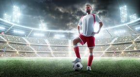 Jogador profissional do futebol que prepara-se ao fósforo Pé na bola de futebol Fundo do estádio da noite Conceito do esporte fotografia de stock