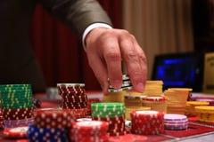 Jogador que coloca microplaquetas em uma tabela de jogo no casino Imagens de Stock