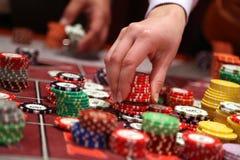 Jogador que coloca microplaquetas em uma tabela de jogo no casino Imagem de Stock