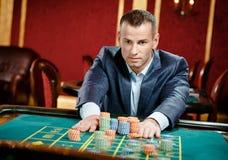 Jogador que coloca uma aposta na tabela da roleta imagem de stock
