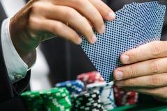 Jogador que joga cartões do póquer com as microplaquetas de póquer na tabela do póquer Fotografia de Stock