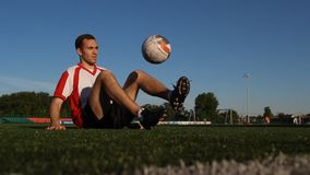 Jogador que senta-se na grama e que salta uma bola de futebol com pés vídeos de arquivo