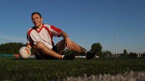 Jogador que senta-se na grama e que salta uma bola de futebol com pés video estoque