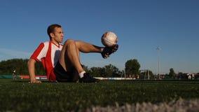 Jogador que senta-se na grama e que salta uma bola de futebol pelos pés vídeos de arquivo