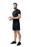 Jogador seguro futsal ou de futebol que guarda a bola com ambas as mãos que olham a câmera Foto de Stock Royalty Free