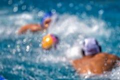 Jogadores borrados das duas equipes na ação durante o polo aquático Imagens de Stock Royalty Free