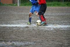 Jogadores das crianças durante um fósforo de futebol em um campo de ação completamente Foto de Stock Royalty Free