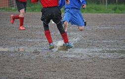 Jogadores das crianças durante um fósforo de futebol em um campo de ação completamente Fotos de Stock