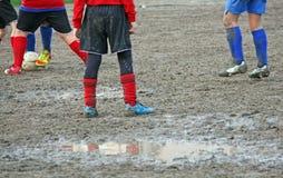 Jogadores das crianças durante um fósforo de futebol em um campo de ação completamente Imagem de Stock Royalty Free