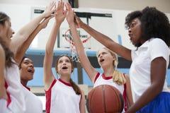 Jogadores de basquetebol fêmeas da High School que juntam-se às mãos durante Team Talk With Coach fotografia de stock royalty free