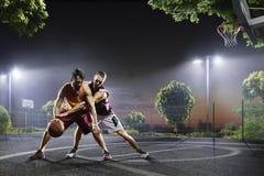 Jogadores de basquetebol na ação na corte Fotografia de Stock Royalty Free