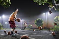 Jogadores de basquetebol que dão certo na corte de noite Fotografia de Stock