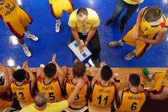 Jogadores de basquetebol recolhidos em torno do treinador imagens de stock