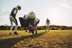 Jogadores de futebol americano que fazem abordando brocas em um campo de esportes imagens de stock royalty free