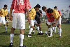 Jogadores de futebol em torno da esfera Fotos de Stock Royalty Free