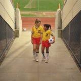 Jogadores de futebol fêmeas novos no campo do estádio Foto de Stock