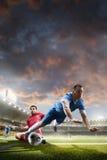 Jogadores de futebol na ação no fundo do estádio do por do sol Fotografia de Stock