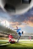 Jogadores de futebol na ação no fundo do estádio do por do sol Foto de Stock