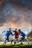 Jogadores de futebol na ação no fundo do estádio do por do sol Imagem de Stock Royalty Free