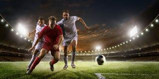 Jogadores de futebol na ação no panorama do fundo do estádio do por do sol