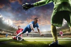 Jogadores de futebol na ação no panorama do fundo do estádio do por do sol Fotografia de Stock