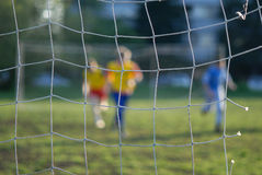 Jogadores de futebol na frente da rede Fotografia de Stock Royalty Free