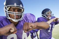 Jogadores de futebol que olham ausentes ao jogar no campo Foto de Stock Royalty Free
