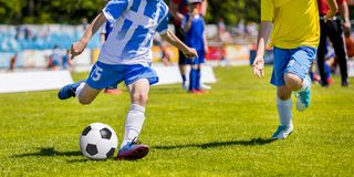Jogadores de futebol running do futebol da juventude Meninos que retrocedem o fósforo de futebol Foto de Stock Royalty Free
