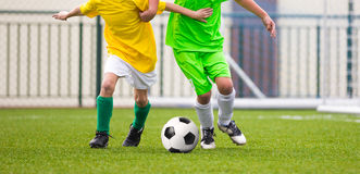 Jogadores de futebol running do futebol das crianças com bola Os jogadores de futebol competem Imagem de Stock