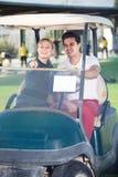 Jogadores de golfe adultos do homem e da mulher que montam o carrinho de golfe Fotos de Stock Royalty Free