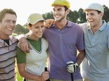 Jogadores de golfe alegres no campo de golfe Fotografia de Stock
