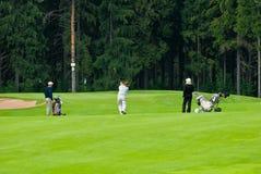 Jogadores de golfe do grupo no feeld do golfe Imagens de Stock