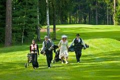 Jogadores de golfe do grupo no feeld do golfe Foto de Stock Royalty Free