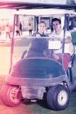 Jogadores de golfe do homem novo e da mulher que montam o carrinho de golfe Imagem de Stock